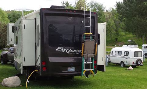 Our Small Travel Trailer parked next to a large motorhome