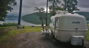 Small travel trailer camped on mountain lake